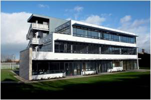 Outside view of the Minola Offices. A 3-story white and grey building with a rectangular, modern design. Located at ITT Dublin, Tallaght, Dublin 24.